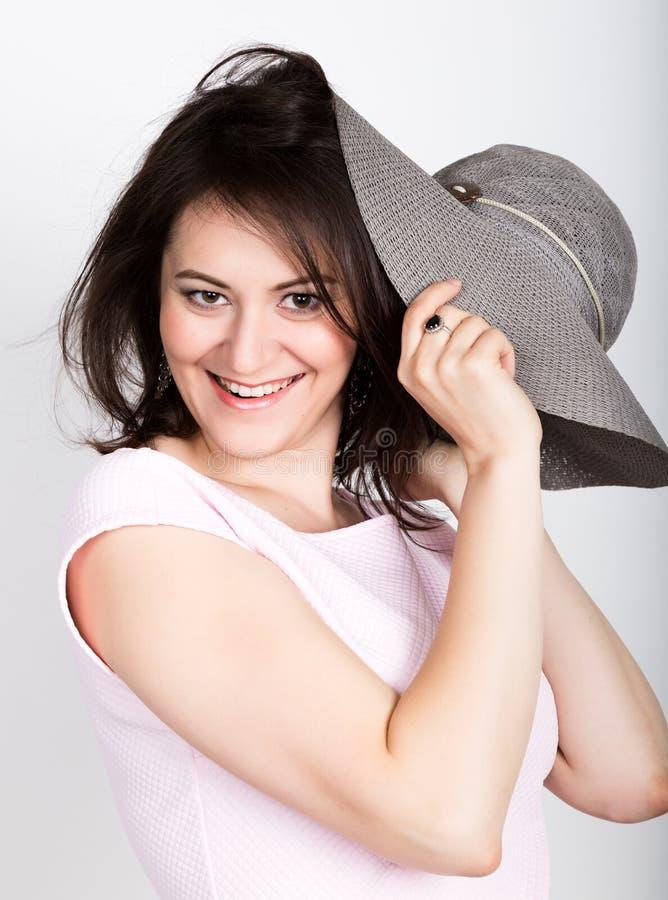 Belle jeune femme de brune tenant un chapeau à bords larges, elle cache son visage derrière un chapeau concept de flirt de fille image stock