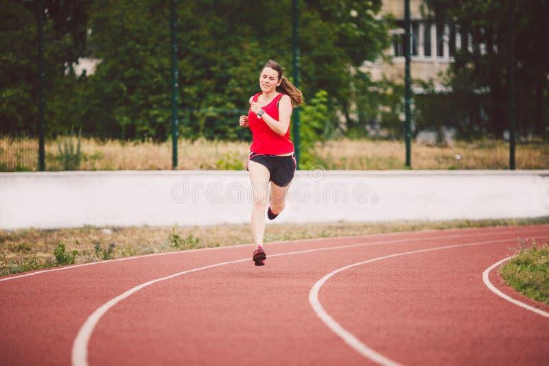 Belle jeune femme de Caucasian d'athlète avec de grands seins dans le T-shirt rouge et les shorts courts pulser, fonctionnant dan image libre de droits
