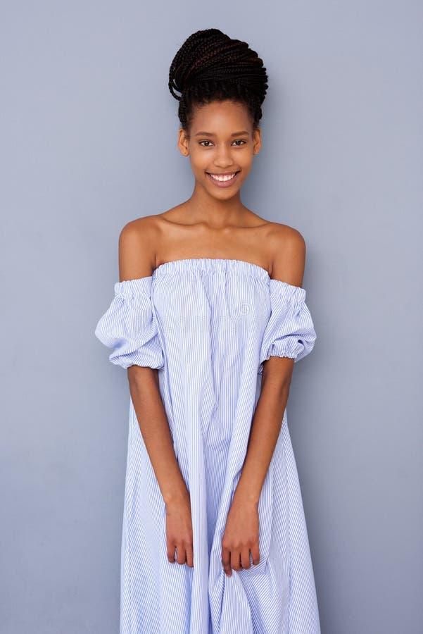Belle jeune femme de couleur dans la robe abaissant le fond gris images stock