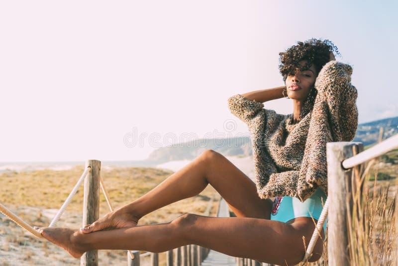 Belle jeune femme de couleur s'asseyant dans un pont en bois de pied à photographie stock