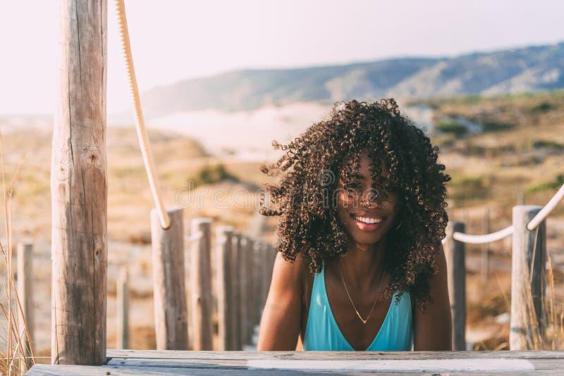 Belle jeune femme de couleur se couchant dans un pont en bois de pied images stock