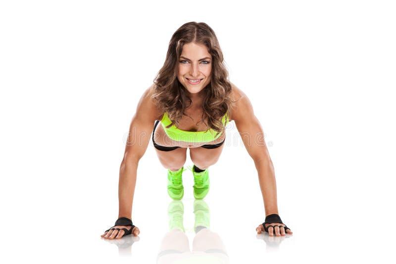 Belle jeune femme de forme physique faisant des pompes photo stock