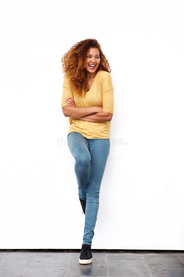 Belle jeune femme de plein corps riant contre le mur blanc images stock