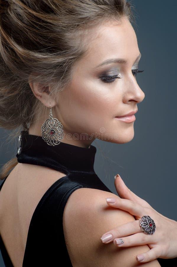Belle jeune femme de portrait en gros plan portant les bijoux de luxe images stock