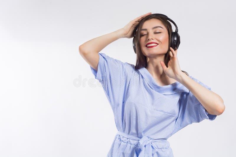 Belle jeune femme de sourire écoutant la musique au-dessus du fond blanc Mode de vie et concept de personnes photo libre de droits