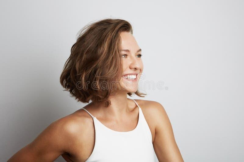 Belle jeune femme de sourire Au-dessus du fond blanc photos stock