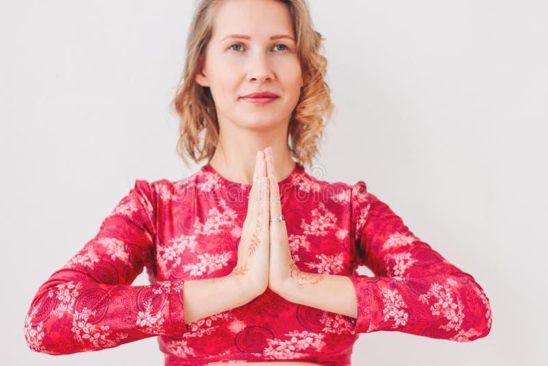 Belle jeune femme de sourire blonde dans l'asana de pratique rouge Namaste de yoga de costume ethnique d'isolement sur le fond bl photographie stock