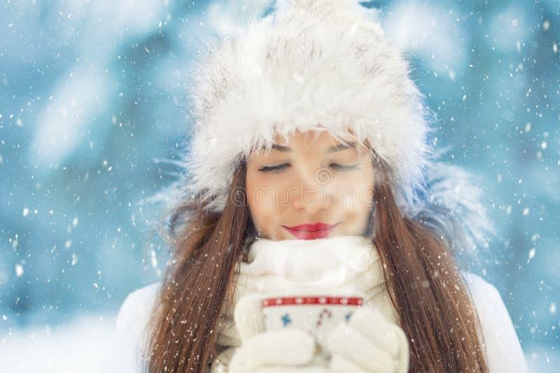 Belle jeune femme de sourire dans l'habillement chaud avec la tasse de chaud image stock
