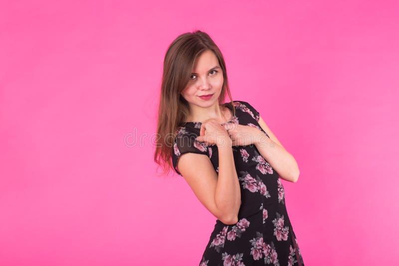 Belle jeune femme de sourire dans la mini robe posant, présentant quelque chose et regardant loin photo libre de droits