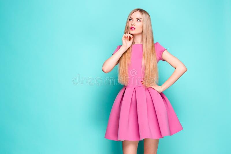 Belle jeune femme de sourire dans la mini robe rose posant, présentant quelque chose et regardant loin Longueur de quart de trois images stock