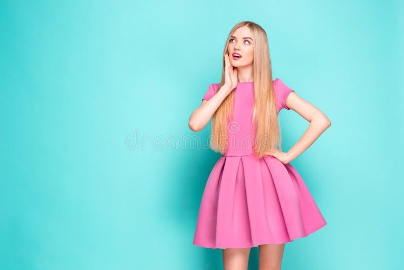 Belle jeune femme de sourire dans la mini robe rose posant, présentant quelque chose et regardant loin Longueur de quart de trois photo libre de droits