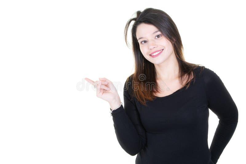 Belle jeune femme de sourire dans le chandail noir occasionnel porter le pointage avec l'espace de copie de doigt et regarder la  image libre de droits