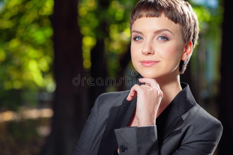 Belle jeune femme de sourire dans le tenue de soirée tenant la main sur le chi photo libre de droits