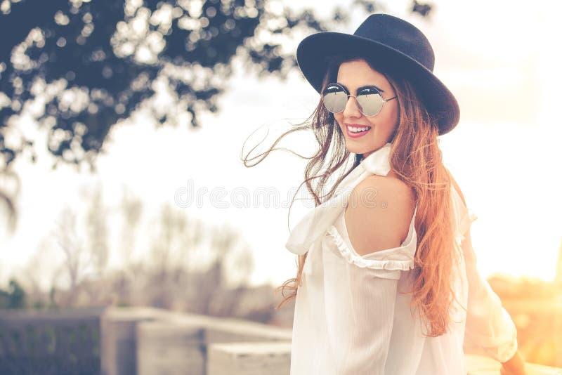 Belle jeune femme de sourire dehors avec les lunettes de soleil et le chapeau, chemise blanche photographie stock libre de droits