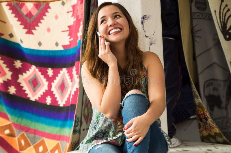Belle jeune femme de sourire employant son celphone, fil de textile traditionnel andin d'habillement et tissé à la main en laine photos libres de droits