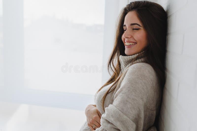 Belle jeune femme de sourire heureuse ? la maison photographie stock libre de droits
