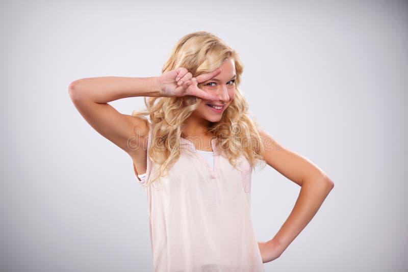 Belle jeune femme de sourire heureuse montrant deux image stock