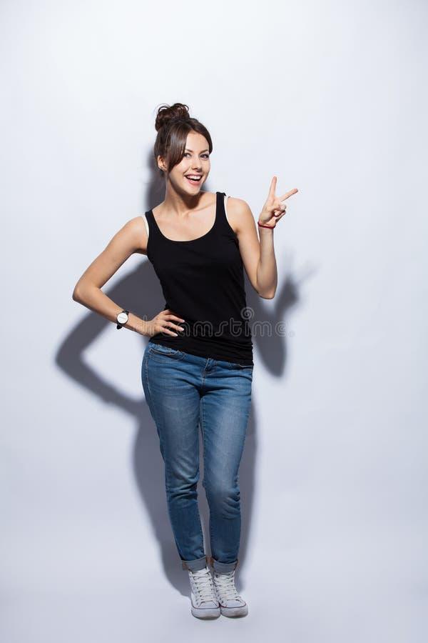 Belle jeune femme de sourire heureuse montrant deux doigts ou gestes de victoire, d'isolement au-dessus du fond blanc images stock