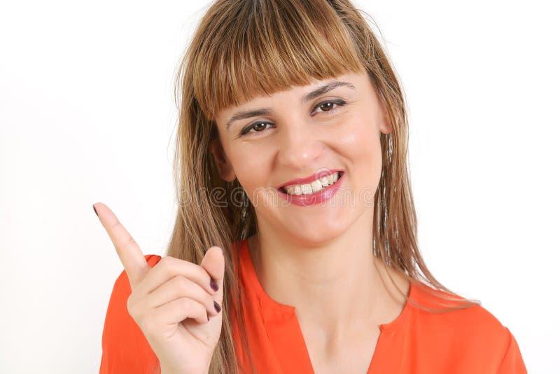 Belle jeune femme de sourire heureuse montrant le copyspace ou le somethi photographie stock
