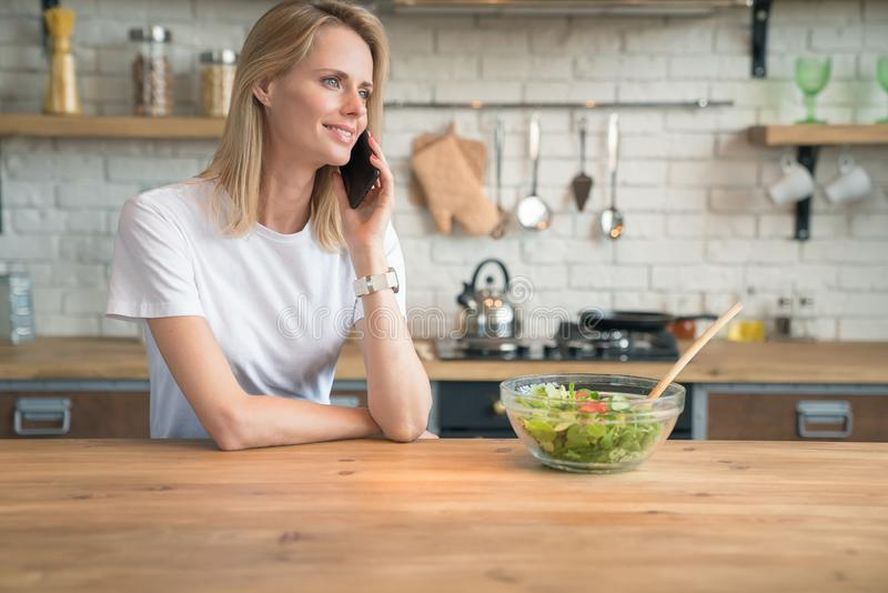 Belle jeune femme de sourire parlant au téléphone tout en faisant la salade dans la cuisine Nourriture saine Salade v?g?tale R?gi image stock