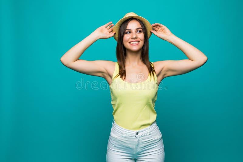 Belle jeune femme de sourire posant avec des mains sur le chapeau sur le fond de turquoise image stock