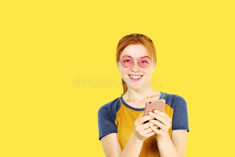 Belle jeune femme dirigée rouge posant, montrant des expressions du visage émotives et faisant les visages drôles avec le télépho images stock