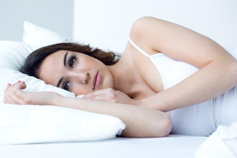 Belle jeune femme dormant dans le lit image stock