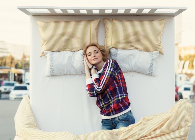 Belle jeune femme dormant dans un lit au centre de la ville photos stock