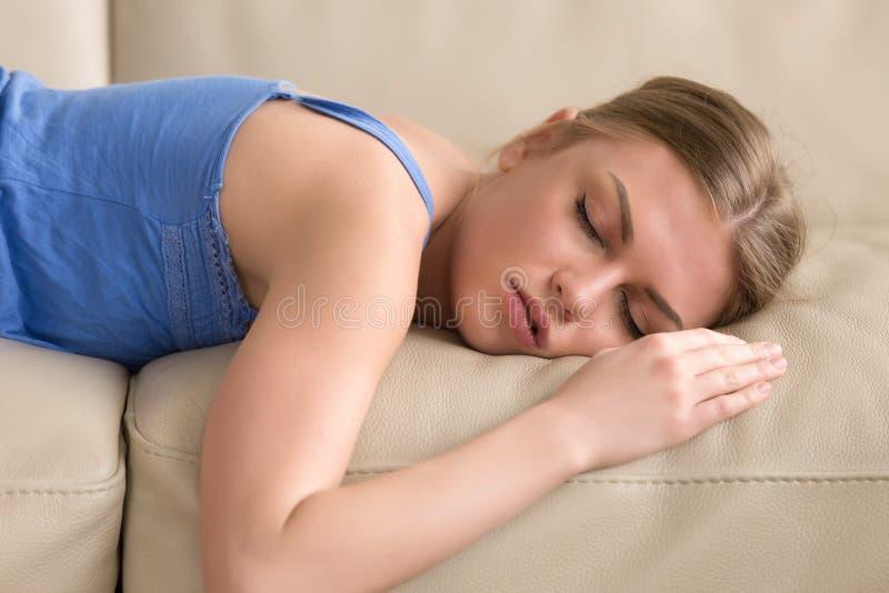 Belle jeune femme dormant sur le divan à la maison, portra de headshot photographie stock libre de droits