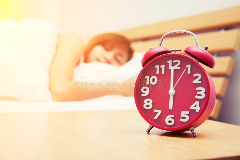 Belle jeune femme dormant sur le lit avec le réveil rouge i images stock