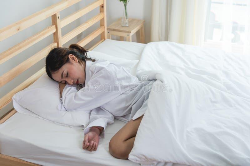 Belle jeune femme dormant sur le lit blanc image libre de droits