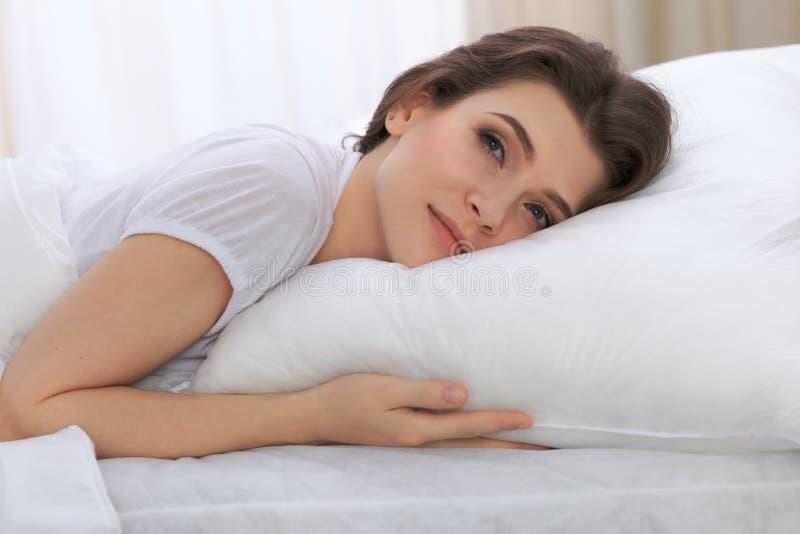 Belle jeune femme dormant tout en se situant dans son lit et détendant confortablement Il est facile de se réveiller pour le trav photographie stock