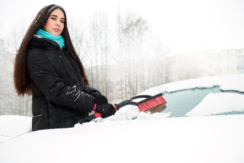 Belle jeune femme drôle enlevant la neige de sa voiture photographie stock libre de droits