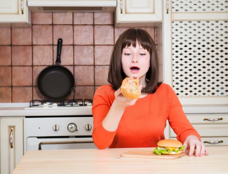 Belle jeune femme drôle mangeant la pizza et l'hamburger de pain français photos stock