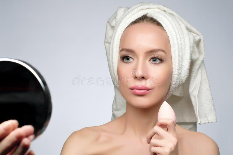 Belle jeune femme employant l'éponge de beauté pour appliquer la base pour le maquillage images libres de droits