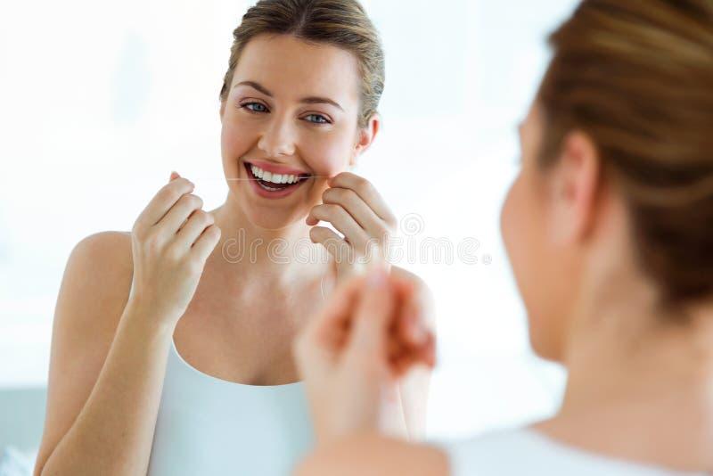 Belle jeune femme employant le fil dentaire dans une salle de bains à la maison photo stock