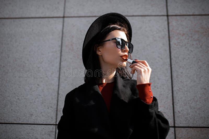 Belle jeune femme en chapeau peint des lèvres images libres de droits
