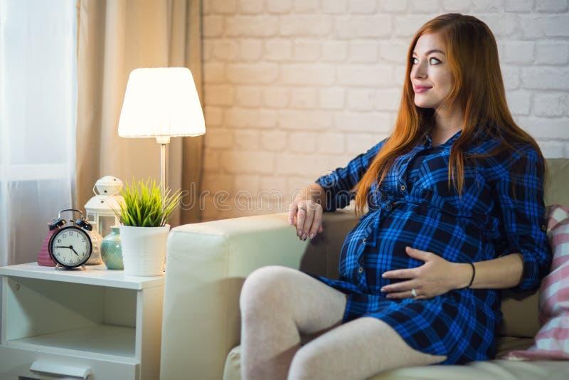 Belle jeune femme enceinte rousse s'asseyant à la maison sur image libre de droits
