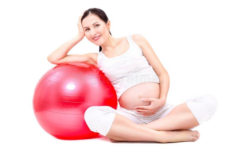 Belle jeune femme enceinte s'asseyant avec le fitball image libre de droits