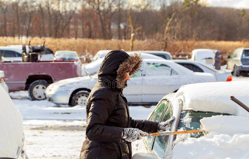 Belle jeune femme enlevant la neige de sa voiture image stock