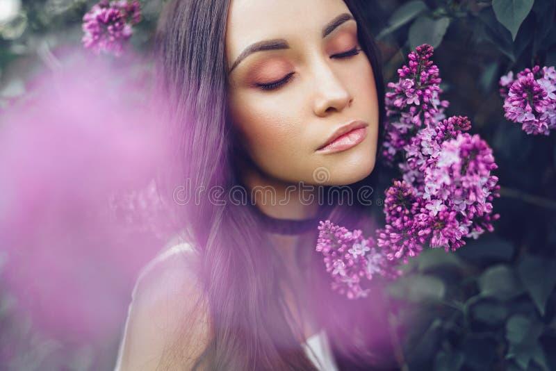 Belle jeune femme entourée par des fleurs de lilas image libre de droits