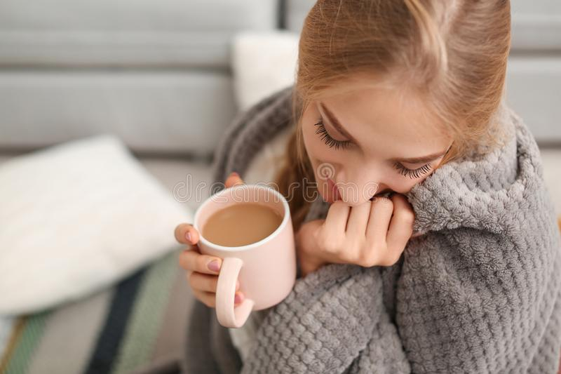 Belle jeune femme enveloppée dans le plaid se reposant avec la tasse de café sur le plancher à la maison photos libres de droits