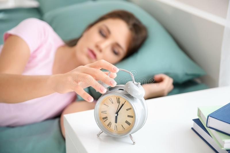 Belle jeune femme essayant d'arrêter le réveil dans le matin photos libres de droits