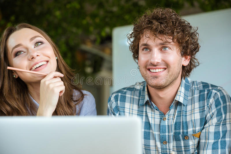 Belle jeune femme et homme bel à l'aide de l'ordinateur portable photo stock