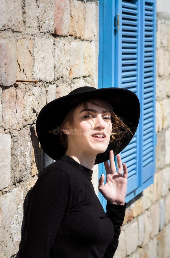 Belle jeune femme expressive dans le noir avec le regard de chapeau noir images stock
