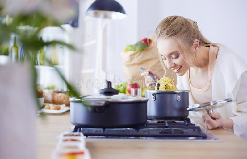 Belle jeune femme faisant cuire dans la cuisine à la maison photos stock