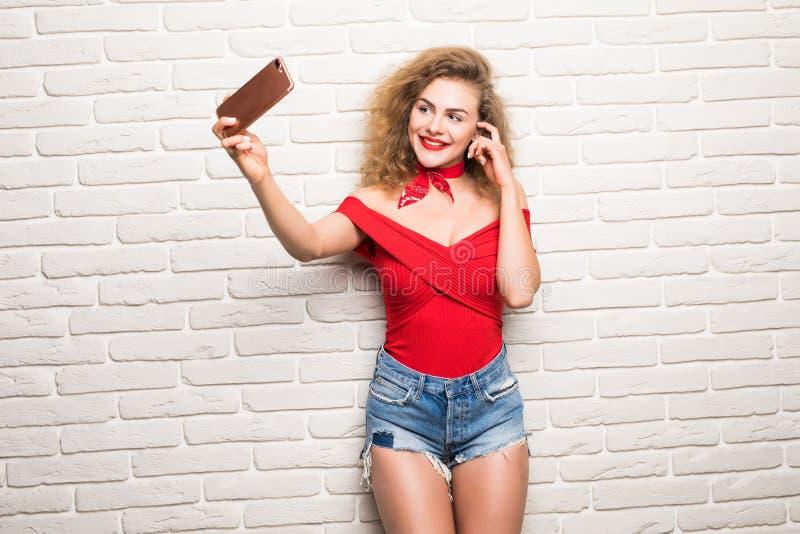 Belle jeune femme faisant l'autoportrait sur un smartphone sur un fond de mur de briques photos stock