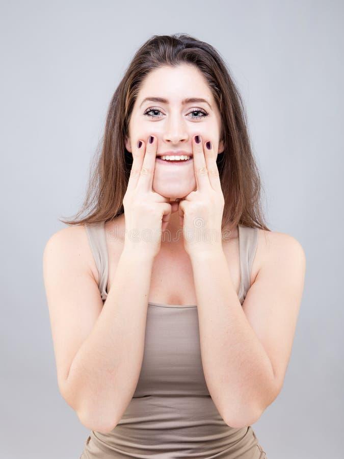 Belle jeune femme faisant la pose de yoga de visage photographie stock