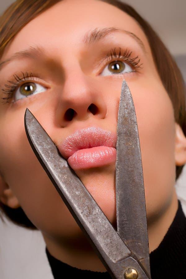 Belle jeune femme feignant pour couper ses languettes photos libres de droits
