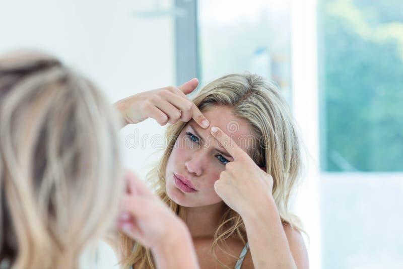 Belle jeune femme focalisée regardant elle-même dans le miroir de salle de bains photos libres de droits